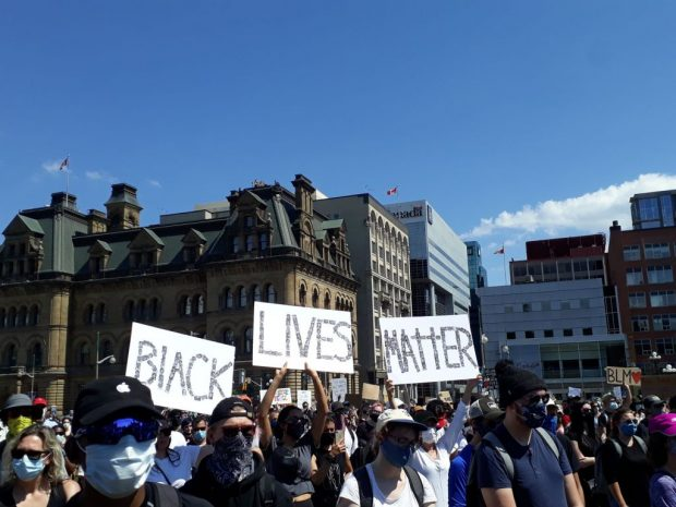 Protestors gather on Parliament Hill with signs raised above their head.