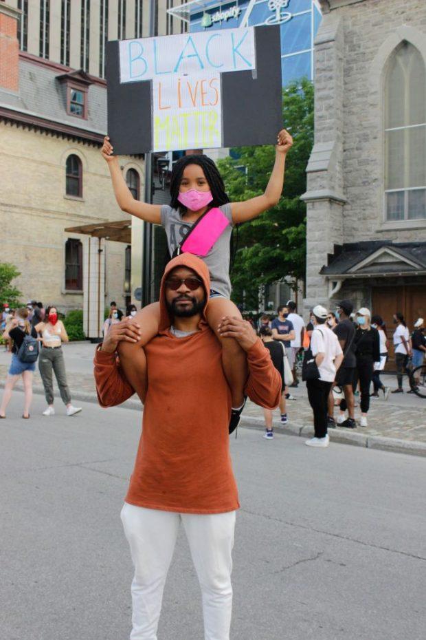 David Muipatayi and his daughter Najya hold a Black Lives Matter sign at the march