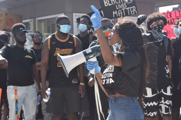 A demonstrator gives an impassioned speech to her crowd in front of the courthouse.