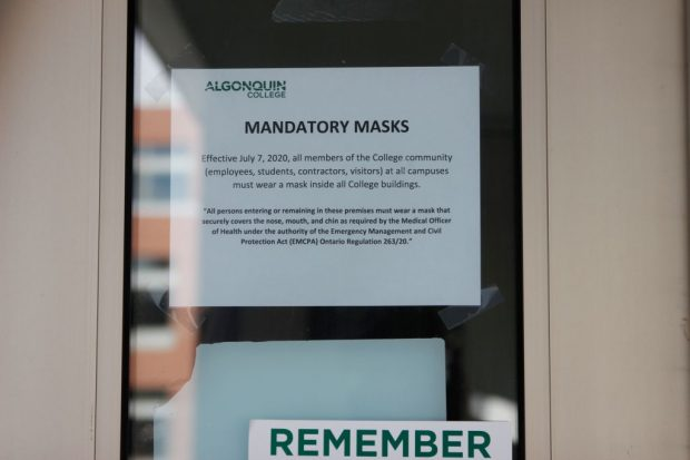 A sign posted on all exterior doors detailing new requirements under COVID-19 as the school slowly comes back to life