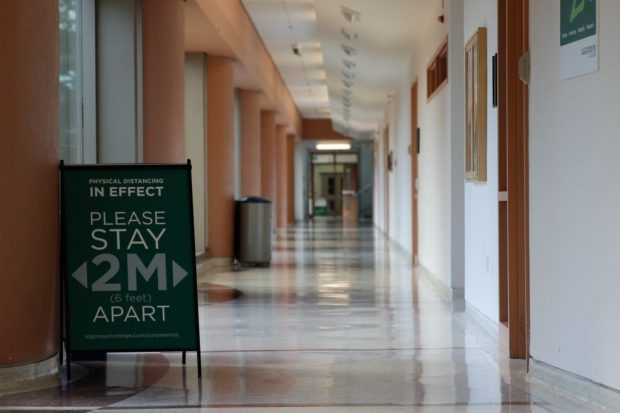 A sign asking students to stand two feet apart stands in an empty corridor