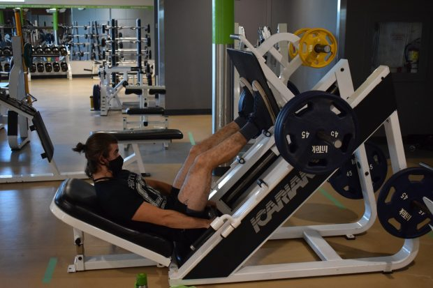 Fitness and health promotion student Vincent Bourdeau works out using the Fitness Zone's leg press machine. The Fitness Zone opened back up for community members Sept. 8.