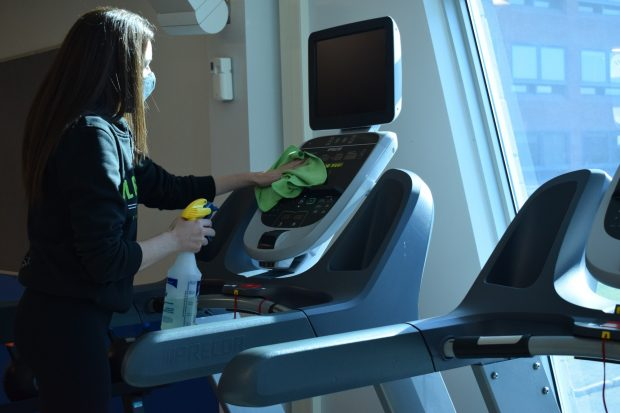Fitness and wellness coordinator Cassandra Jones St-Onge sanitizes a treadmill in the Fitness zone. The Fitness Zone reopened Sept. 8 for community members.
