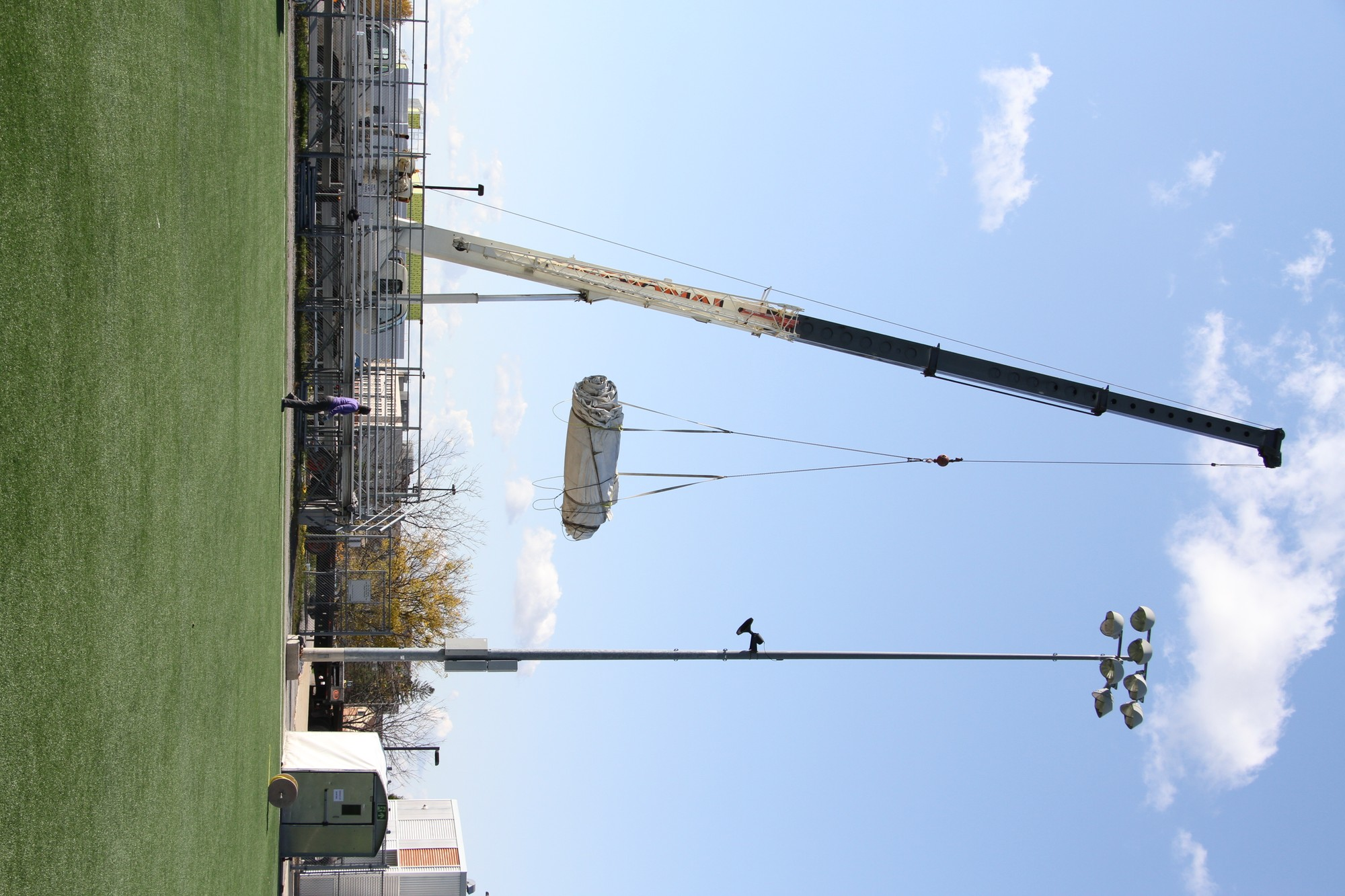 Martha Peak, senior manager of Athletics and Recreation, walks by as the crane lifts the largest tarp off the field.