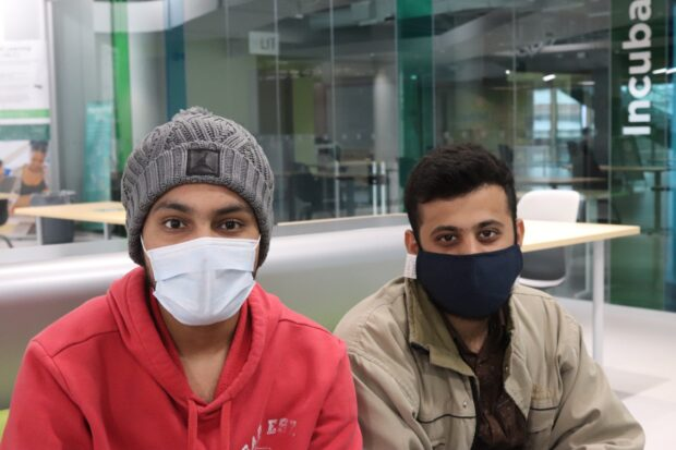 Electrical engineering technician students Gurpartap Singh (left) and his classmate Aditya Shah (right) studying together in the Dare District.