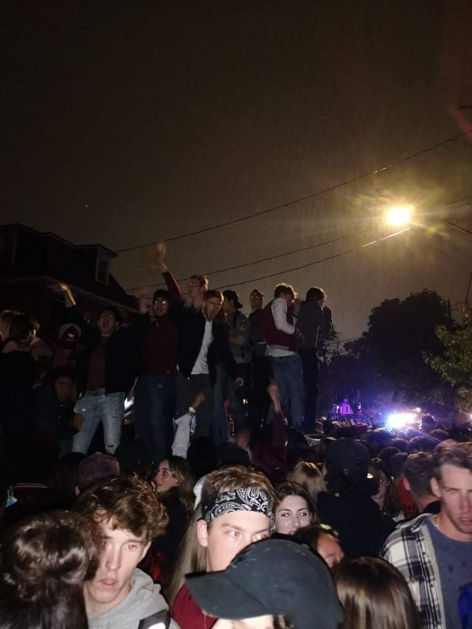 Partygoers on top of the overturned car during the street party.